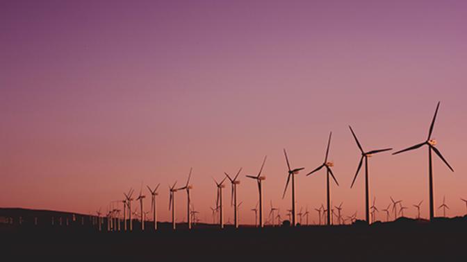 A wind turbine farm at dusk.